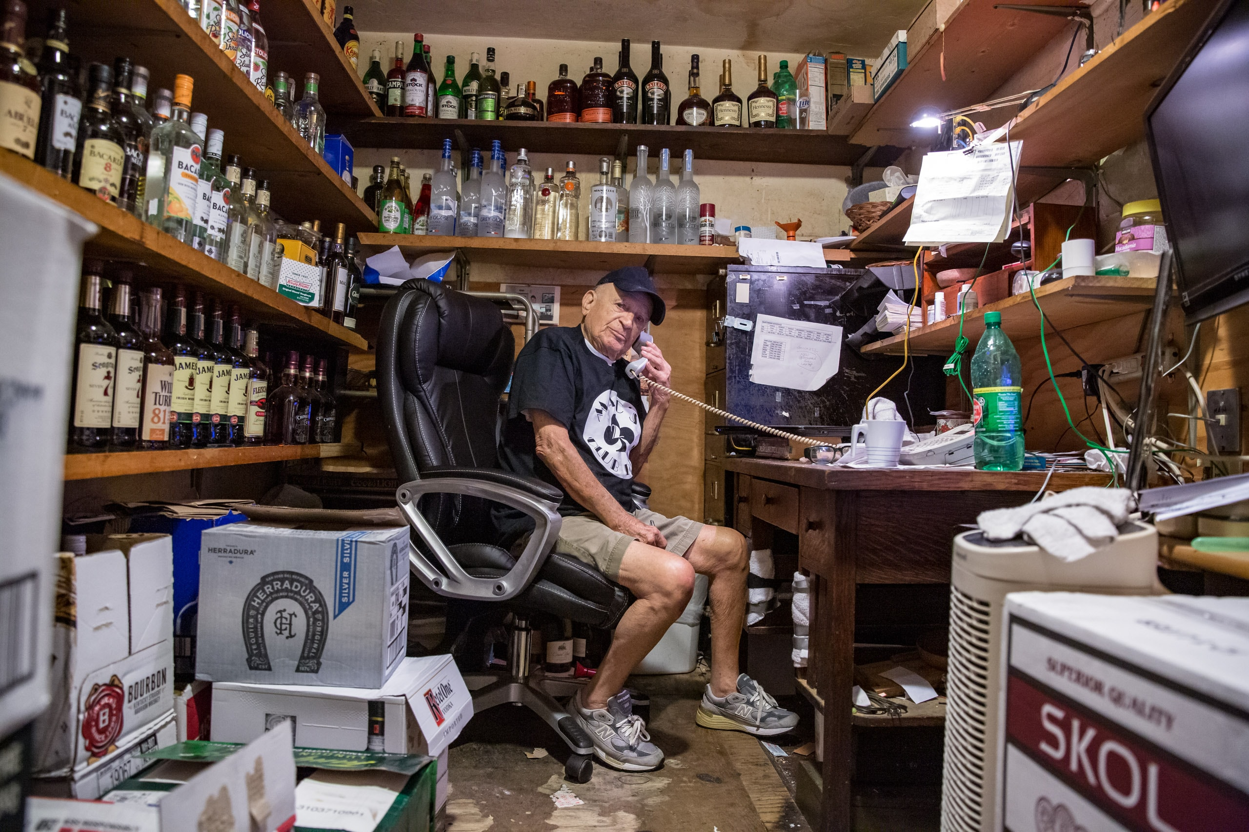 Wide shot into the storage room of a South Beach, Miami cocktail bar. This storage room is also the office of the 100 year old owner and operator of the bar. He is on the corded landline phone and looking dismisively into the camera lens. This photograph is part of the To Live 10,000 Years series by Danny Goldfield.